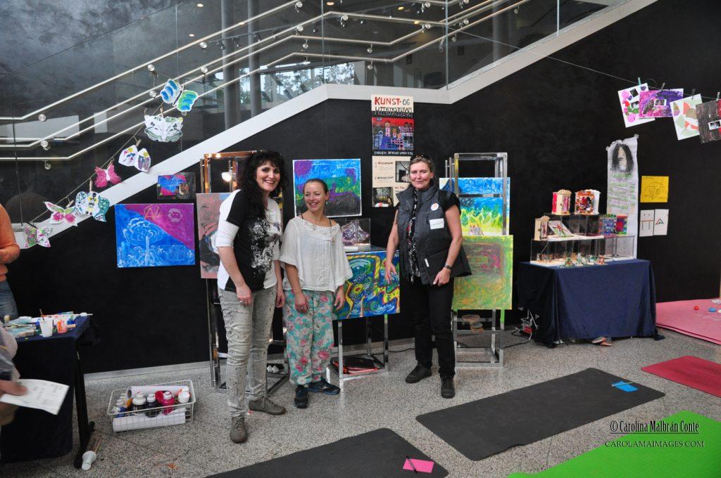 Carolina, Kari Anne og prosjektansvarlige, Irene Sandved, viser stolt frem malerier og keramikk laget av flyktninger under kunstuttrykks-workshop.
